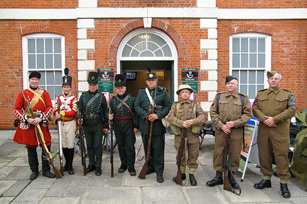 Image of men in historical military uniform standing outside the museum